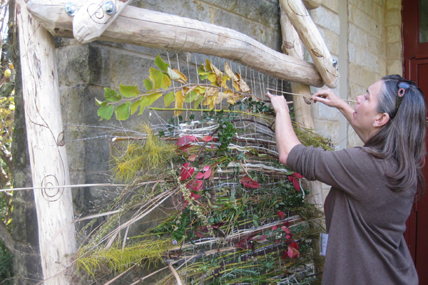 Karen Kelly Mullin of Willow Oak Group, weaves on the Brookside Gardens EarthLoom, November 2013. The weaving includes Amsonia, Rosemary, Holly, and Spearmint.  image: Cheryl Corson