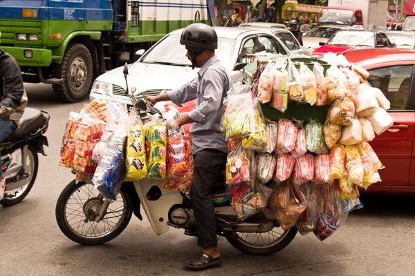 Hawker (vendor) in traffic, Kuala Lumpur, Malaysia  image: Erik Mustonen