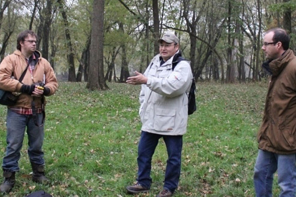 Bill Quackenbush, THPO of the Ho-Chunk Nation of Wisconsin, explaining the significance of the Sny-Magill site at Effigy Mounds National Monument to project team members Paul West, ecologist, and William Whittaker, archeologist. / image: QEA